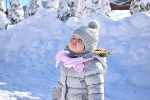 petite fille d'une famille issue de l'immigration qui respire le bonheur dans un paysage enneigé du Québec